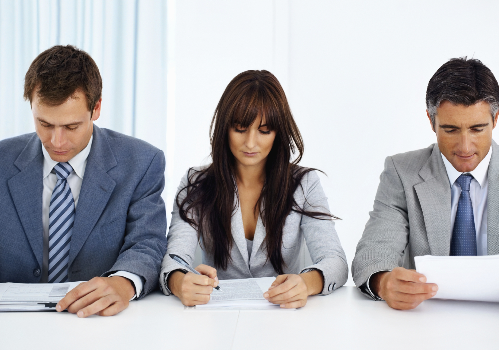 Three business people analyzing documents